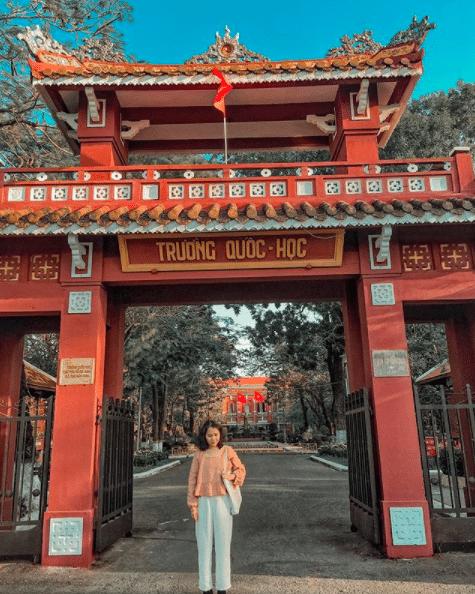 Tham quan Quốc học Huế, bạn sẽ được chiêm ngưỡng công trình mang sắc đỏ rực rỡ cạnh dòng sông Hương thơ mộng
